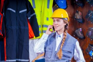 Women with braided brown hair wearing a yellow construction helmet while holding up an iPhone to her right ear.